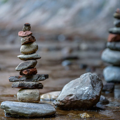 Balance and wellness concept. Close-up of river stones balanced in the shallow mountain creek. Low depth of field. Zen and spa inspired